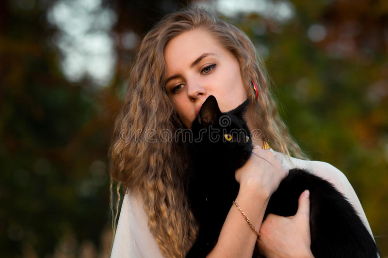 Cute,beautiful,lovely girl with black cat.Upset girl held and caress black cat outdoors in green dark forest. royalty free stock images