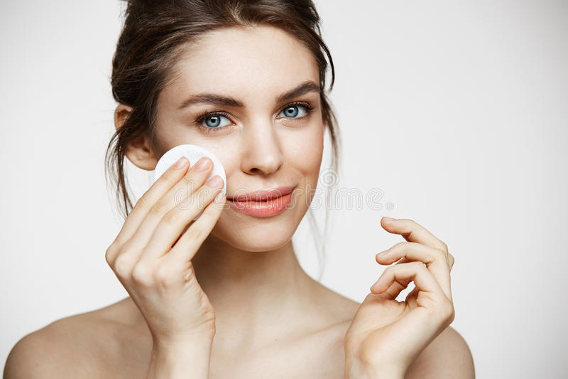 Cute beautiful natural brunette girl cleaning face with cotton sponge smiling looking at camera over white background stock images