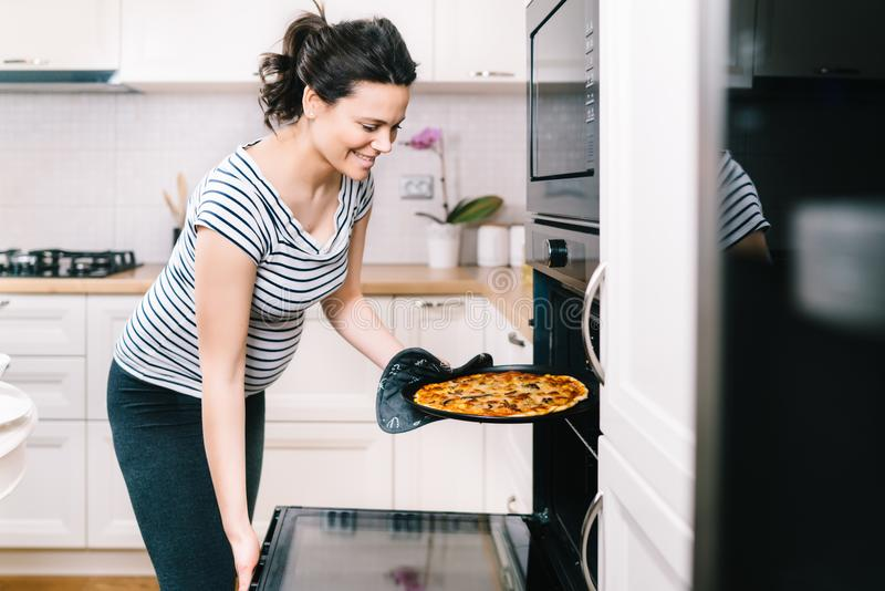 Beautiful pregnant woman in home kitchen preparing pizza and baking royalty free stock image