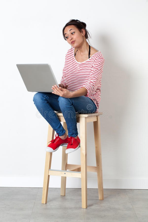 Cute beautiful young woman enjoying communicating on her pc stock photo