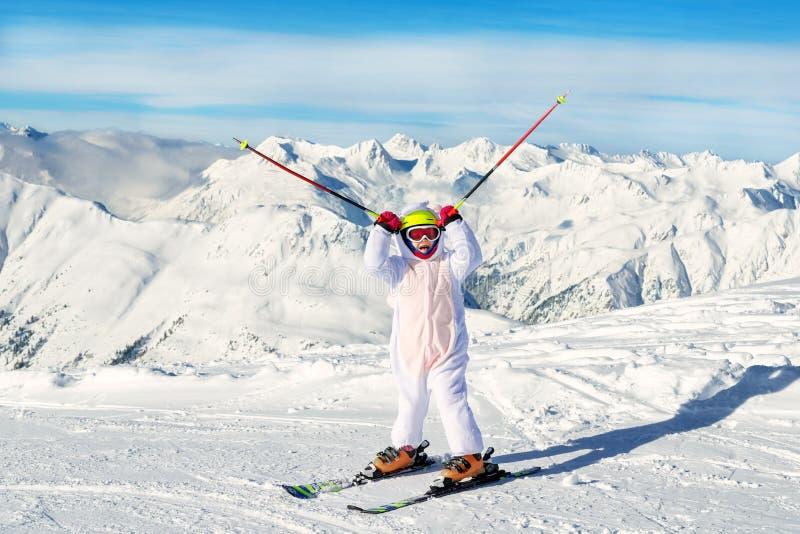 Cute bezauberndes Kinderportrait mit Ski in Helm, Brille und Einhornspusskostüm genießen Wintersport lizenzfreies stockbild