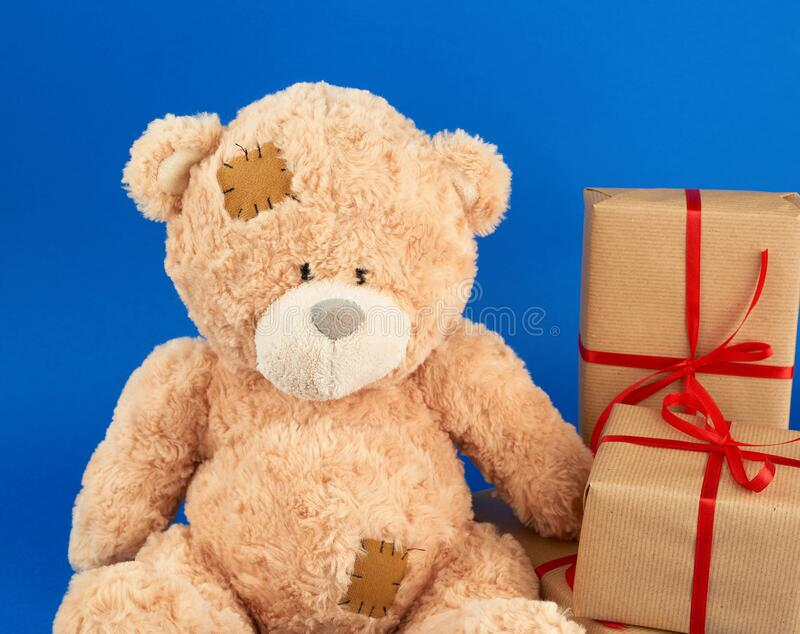 Cute big beige teddy bear holds a brown box with a red ribbon. On a blue background. Festive concept stock photos