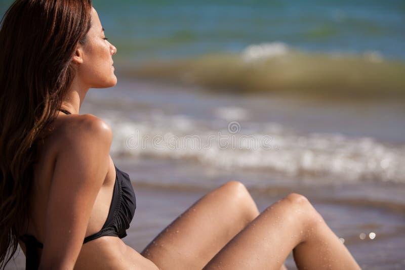 Cute bikini girl getting a suntan. Beautiful young woman on a bikini sunbathing at the beach royalty free stock image