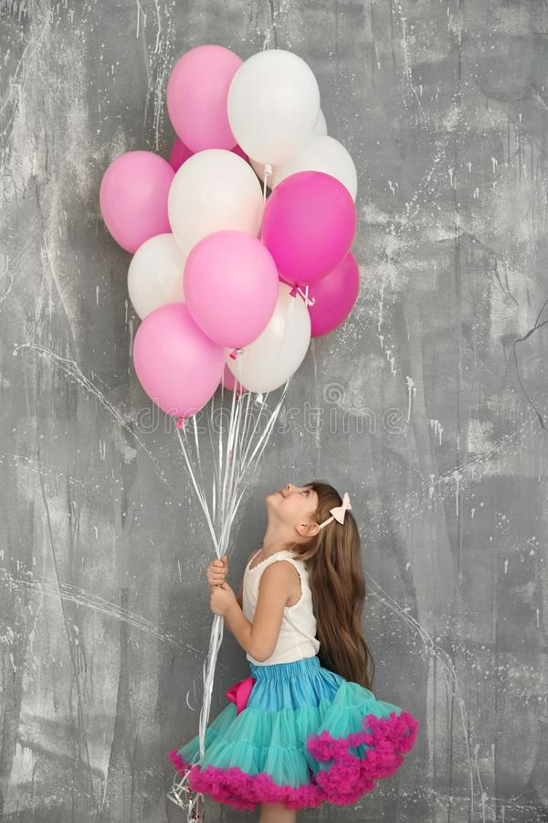 Cute birthday girl with colorful balloons near grunge wall stock images