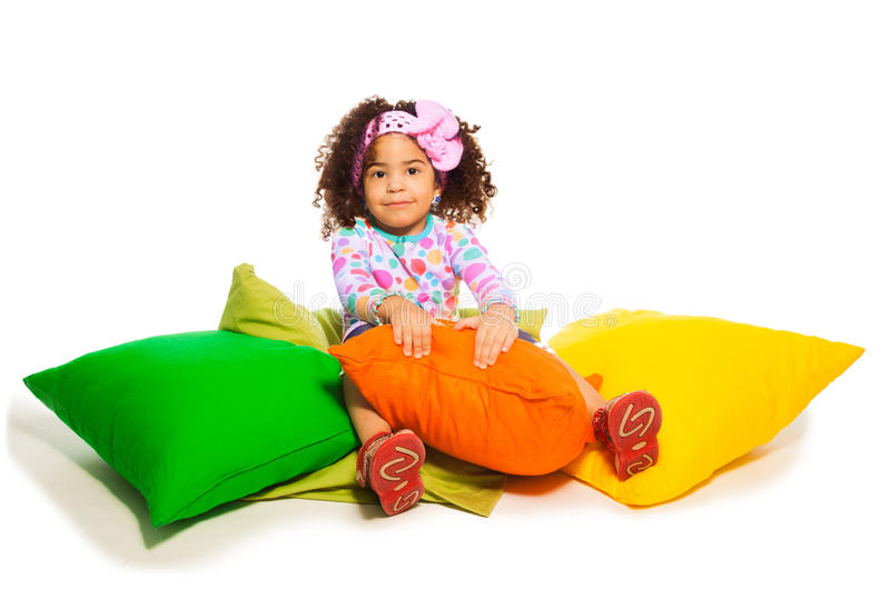 2 years old girl sitting in the pillows. Cute black curly two years old girl sitting in the pillows, isolated on white stock photo