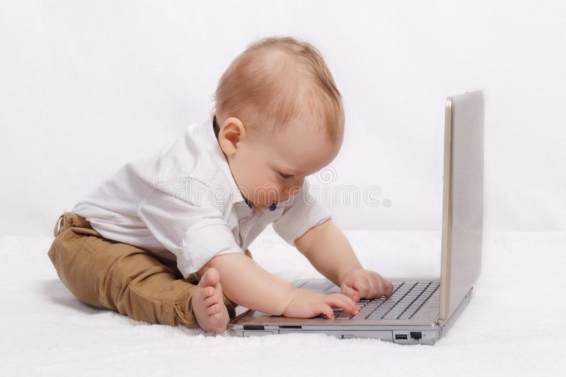 Cute blond baby boy working with laptop. royalty free stock photo