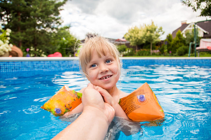 A cute blond baby girl at swimming pool with blue colored water , hold parent`s hand and fells happy. stock photo