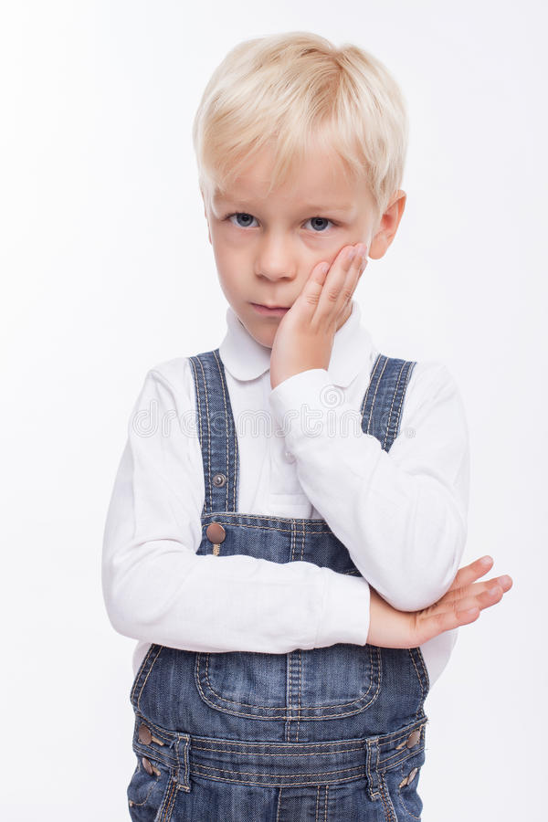Cute blond boy has feelings of boredom. Pretty male child is bored. He is looking at the camera with sadness. The schoolboy is standing and touching his cheek stock photo