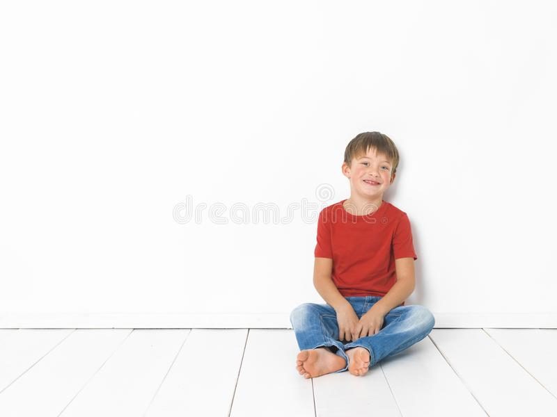 Cute and blond boy with red shirt and blue jeans is posing on white wooden floor stock images