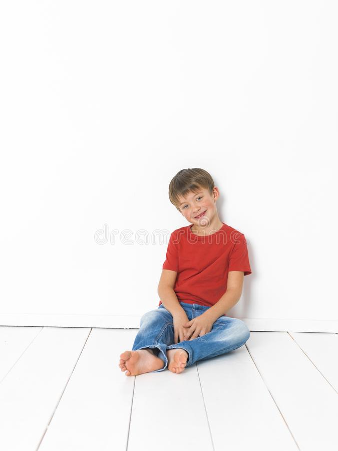 Cute and blond boy with red shirt and blue jeans is posing on white wooden floor stock image
