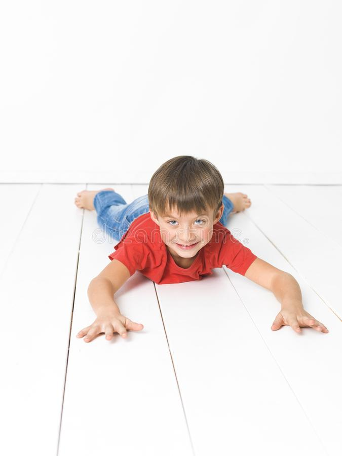 Cute and blond boy with red shirt and blue jeans is posing on white wooden floor royalty free stock photo