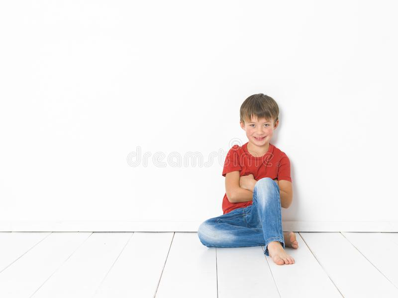 Cute and blond boy with red shirt and blue jeans is posing on white wooden floor royalty free stock image