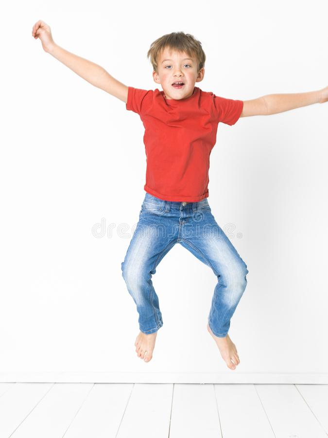 Cute and blond boy with red shirt and blue jeans is posing on white wooden floor royalty free stock photos