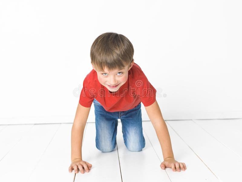 Cute and blond boy with red shirt and blue jeans is posing on white wooden floor stock photo