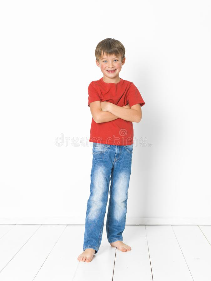 Cute and blond boy with red shirt and blue jeans is posing on white wooden floor royalty free stock images