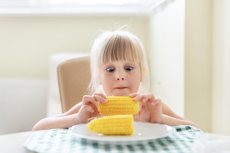 Cute blond caucasian girl holding in hand tasty boiled sweet corn cob and lokking on it with amazed wide opened eyes. Child loves stock images