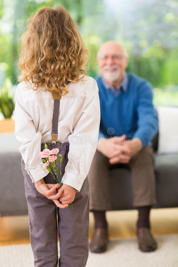 Cute blond child standing with flowers behind her back on the grandfather`s day royalty free stock photos