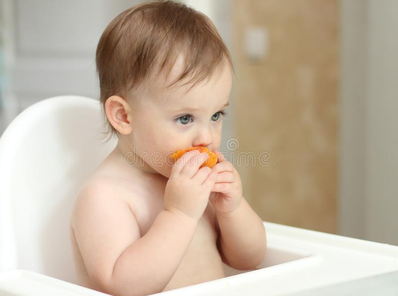 cute blond child sits in a children& x27;s chair at the kitchen and eat a juicy peach. Little girl with a piercing look stock image