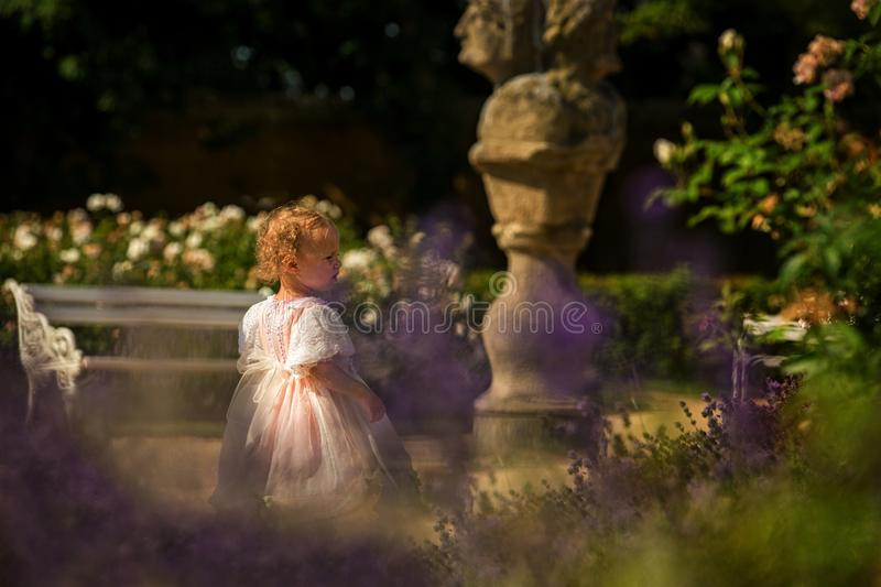 Cute blond curly girl dressed up as princess in the garden of ancient castle, beautiful small girl in pink long dress, fairy tale stock photography