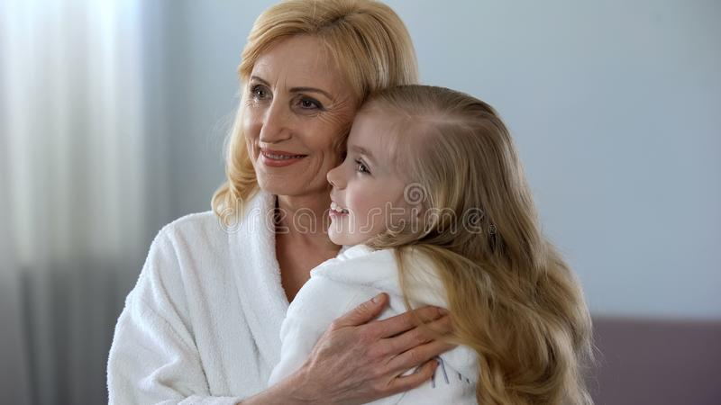 Cute blond female child hugging her beautiful grandmother in morning, care stock photo