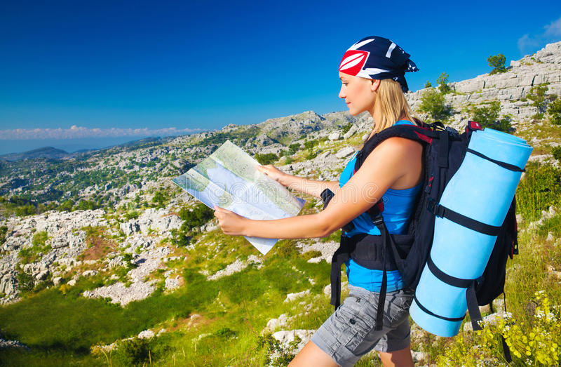 Cute girl in mountains looking to map. Cute blond girl in the mountains looking way on the map, summer vacation, active lifestyle, tourism and expedition concept royalty free stock photography