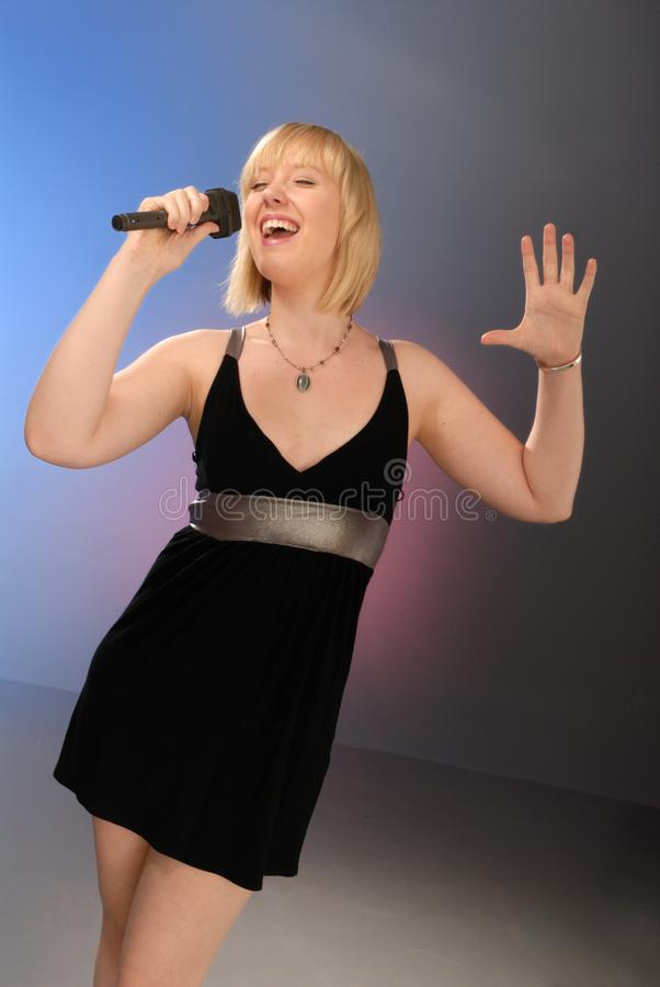 Cute blond girl singing stock photography