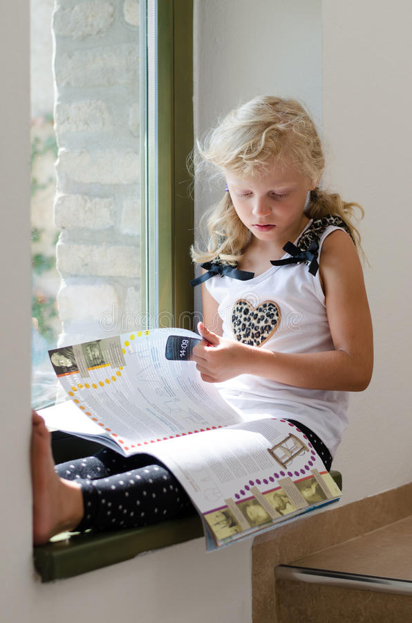 Cute blond girl sitting and reading book stock photo
