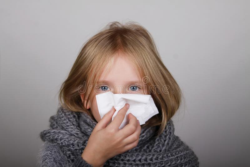 Cute blond hair little girl blowing her nose with paper tissue. Child winter flu allergy health care concept royalty free stock images
