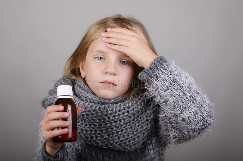 Blond hair little girl holding cough syrup in a hand. Sick child.. Child winter flu health care concept stock photo