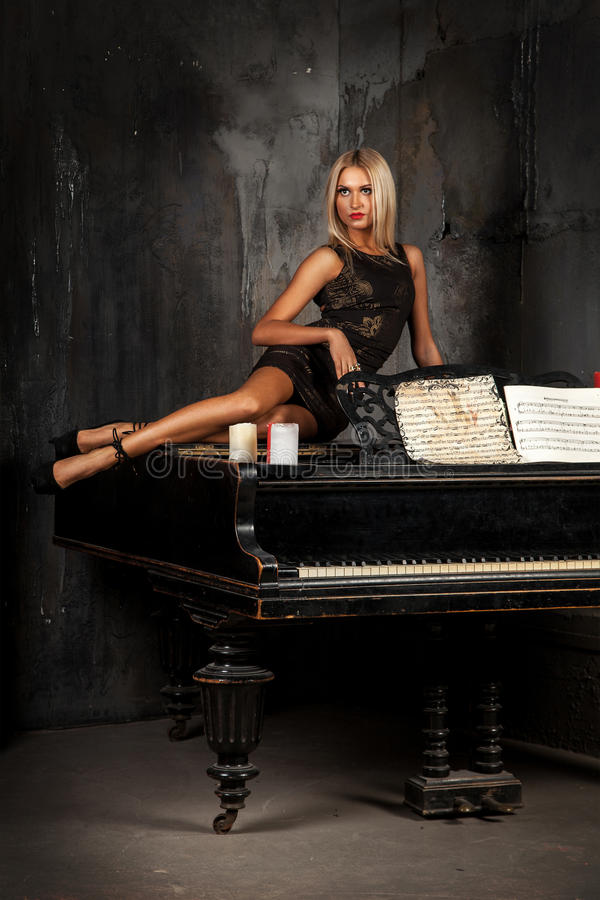 Cute Blond Hair Woman Lying On Piano And Looking Away