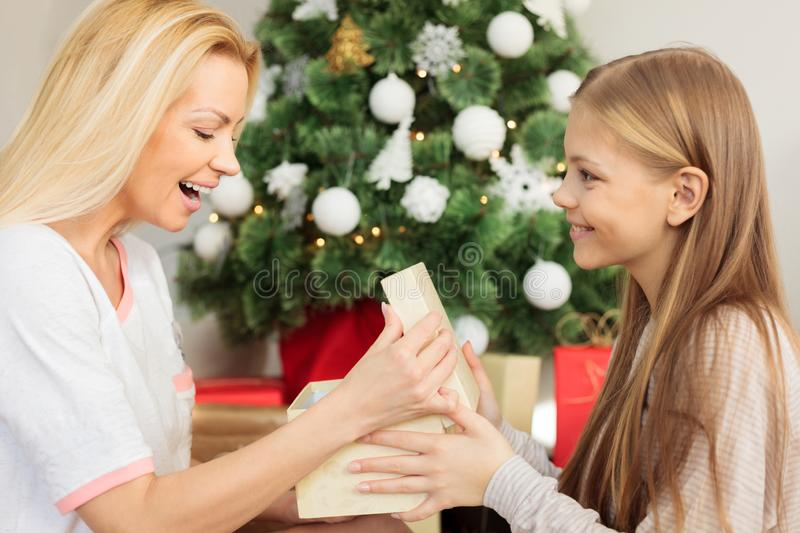Cute blond haired teenage girl giving Christmas gift to her mother. Sitting on the floor in front of a decorated Christmas tree. One parent with one child royalty free stock images