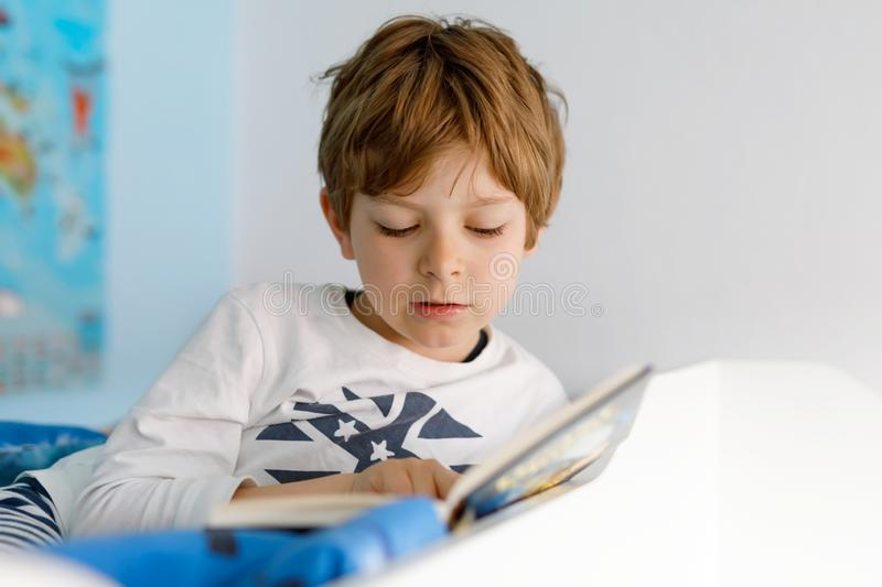 Cute blond little kid boy in pajamas reading book in his bedroom. Excited child reading loud, sitting in his bed royalty free stock photos