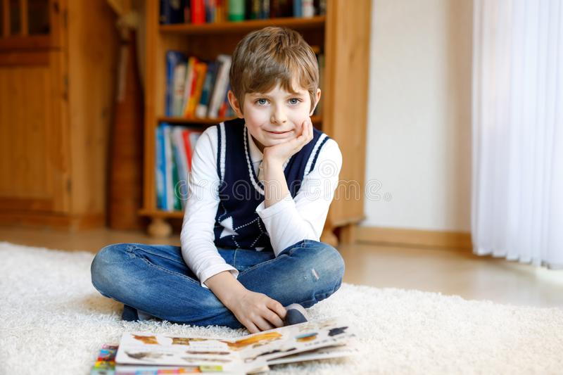 Cute blond little kid boy reading magazine in domestic room. Excited child reading loud. royalty free stock photo