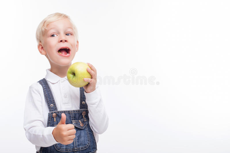 Cute blond schoolboy is enjoying green fruit. Pretty hungry boy is eating a healthy apple with happiness. He is standing and giving thumb up with satisfaction stock photo