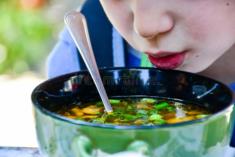 Child eating a soup royalty free stock photos