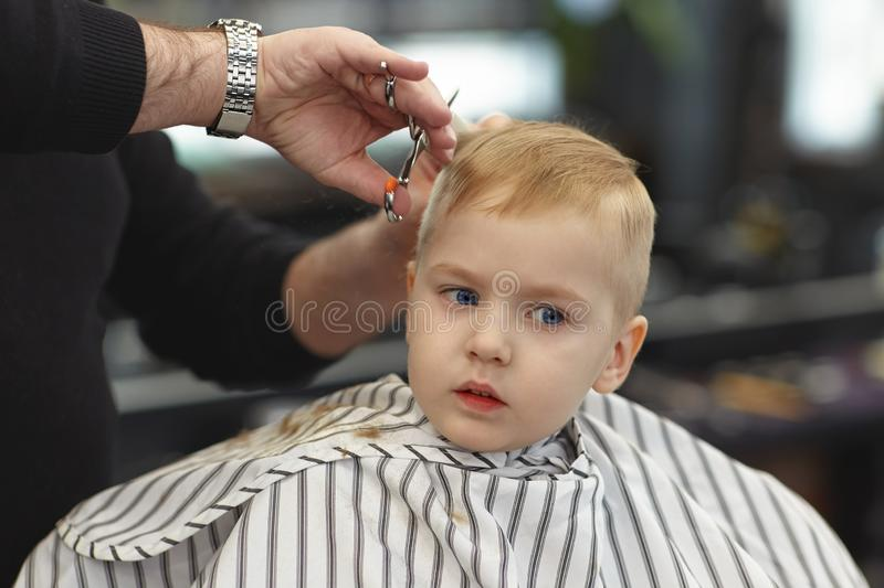 Cute blond smiling baby boy with blue eyes in a barber shop having haircut by hairdresser. Hands of stylist with tools. Children f. Ashion. Indoors, dark royalty free stock image