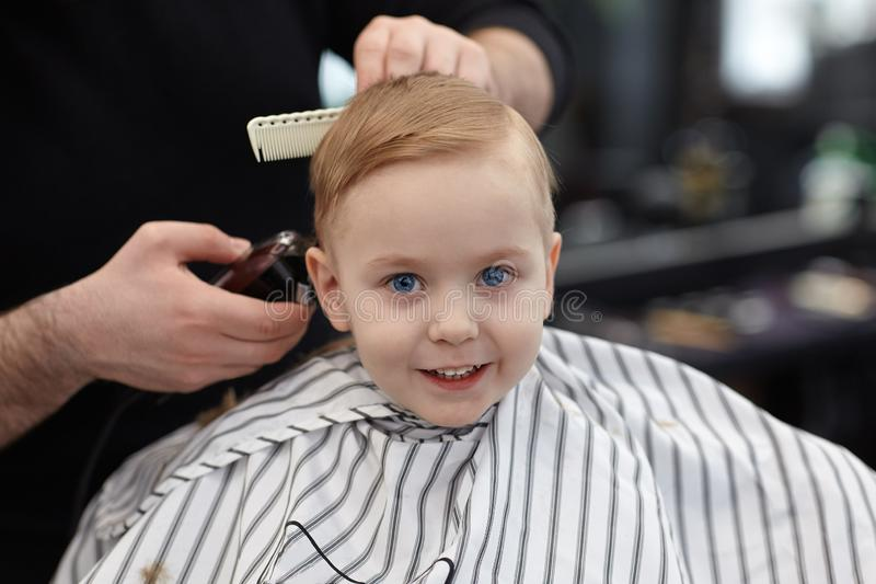 Cute blond smiling baby boy with blue eyes in a barber shop having haircut by hairdresser. Hands of stylist with tools. Children`s stock image