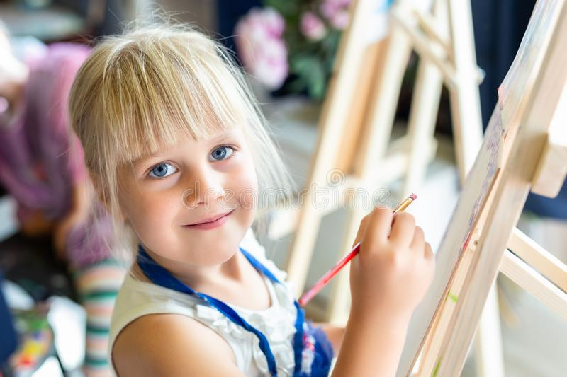 Cute blond smiling girl painting on easel in workshop lesson at art studio. Kid holding brush in hand and having fun drawing with royalty free stock photo