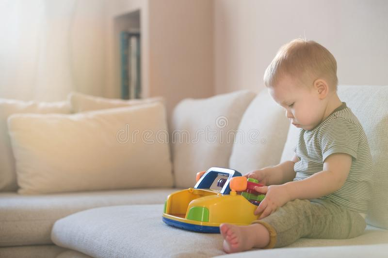 Cute blond toddler boy sitting on the sofa in the living room and playing with a toy. Early learning for kids royalty free stock images
