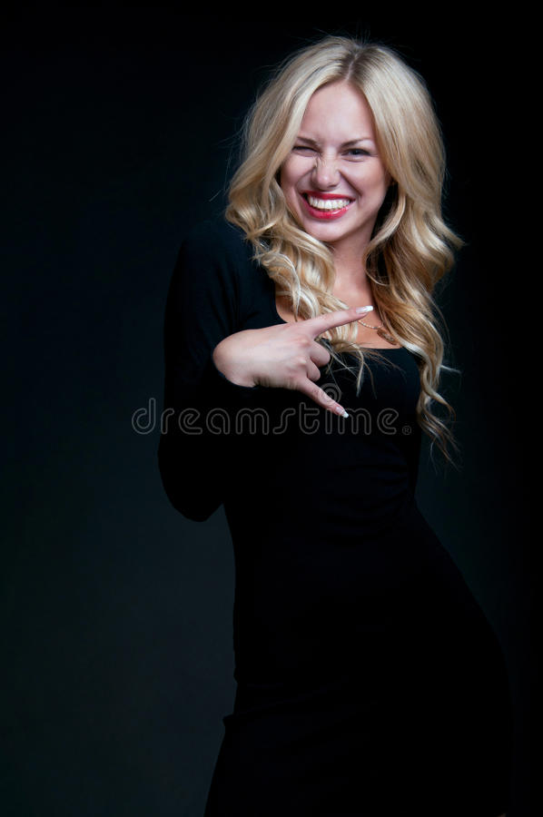 Cute blond woman. Fashion portrait of pretty slim blond woman model with amazing figure wearing black tight cocktail dress, red lipstick, her hair made in locks royalty free stock photos