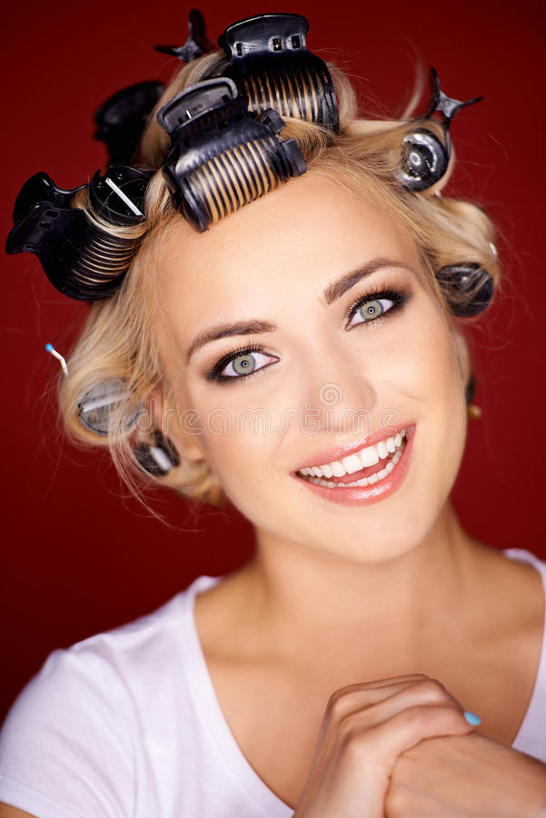 Cute blond woman with her hair in curlers stock photos