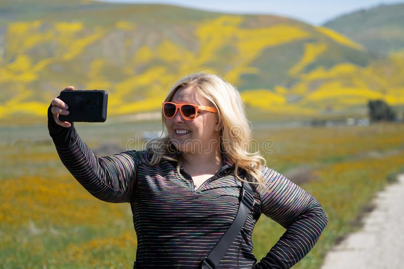 Cute blond woman wearing sunglasses takes selfies at Carrizo Plain National Monument during the California superbloom of royalty free stock photos