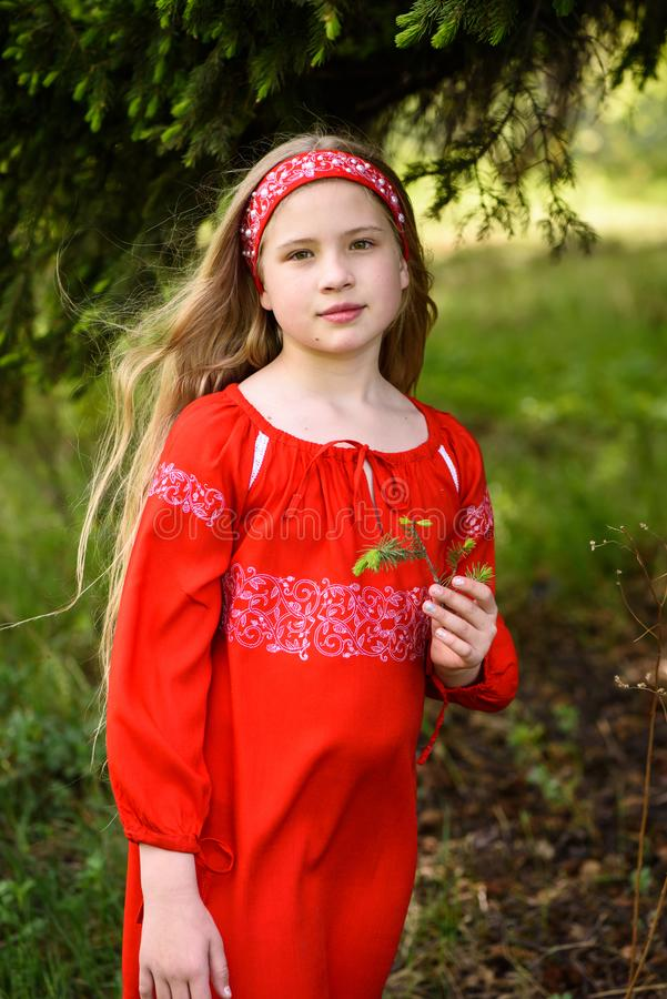 Cute blond young girl posing in a russian traditional red dress near fir tree. In a sunny day stock images