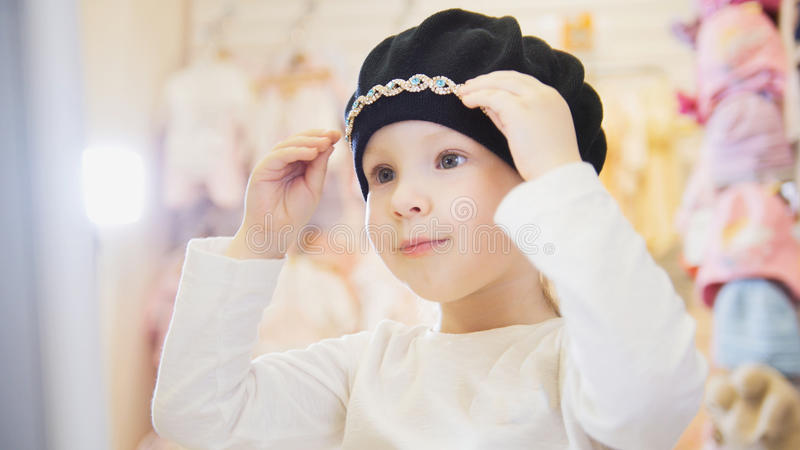 Cute blonde baby girl in kids dress store chooses cute hat royalty free stock photo