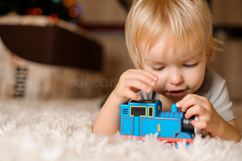 Cute blonde baby playing on the carpet stock photography