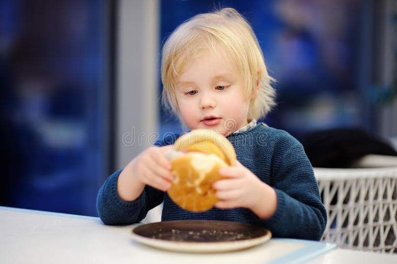 Cute blonde boy eat hamburger at fast food restaurant stock images