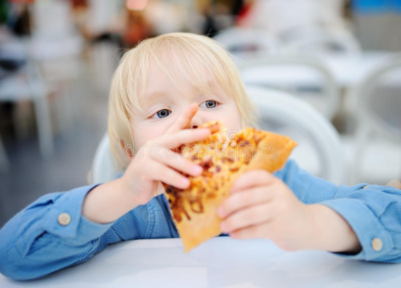 Cute blonde boy eating slice of pizza at fast food restaurant stock photo