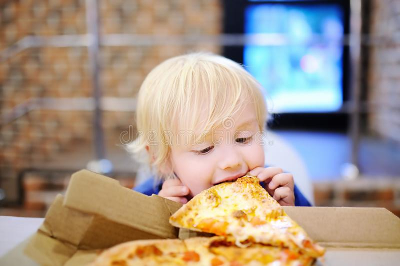 Cute blonde boy eating slice of pizza at fast food restaurant stock images