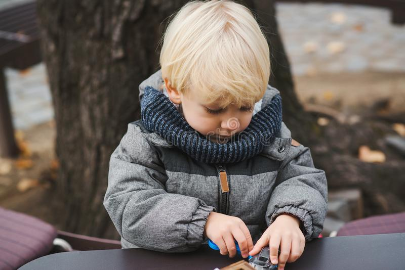 Cute blonde boy playing with toys outdoors. Happy and healthy childhood. Baby boy on a walk in cold autumn day royalty free stock photography