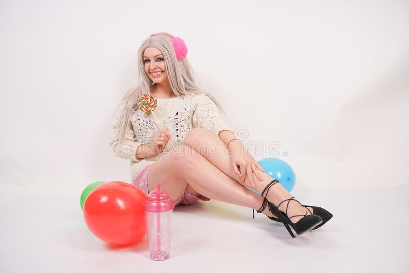 Cute blonde caucasian happy girl dressed in a milky color knitted sweater and funny shorts, she sits on the white floor alone with. Balloons and a glass of stock photography